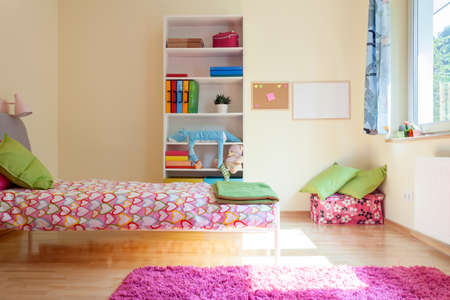 Bright yellow room with pink decorations for girl photo
