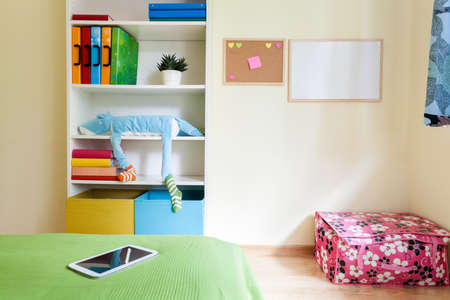 Colorful kids room with comfortable bed and white bookcase photo