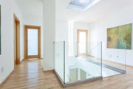 Stairs, glass banister and doors in modern hallway on the attic Standard-Bild