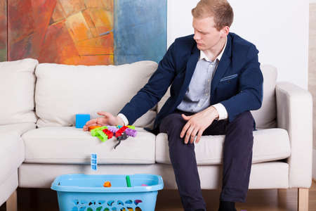 Horizontal view of businessman cleaning childs toys photo