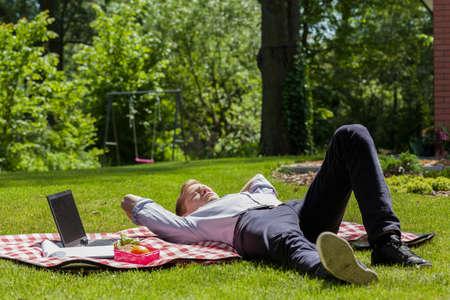 weekend activities: Working man resting in a garden, horizontal
