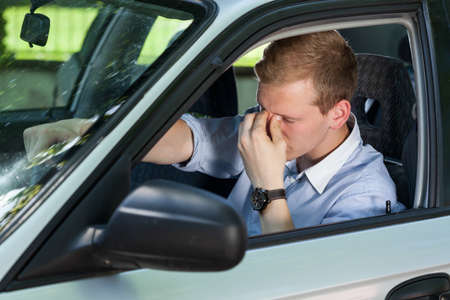 Vista de hombre de negocios cansado de conducir un coche
