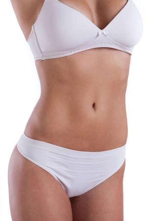 abdomens: Closeup of slim female abdomen on white background