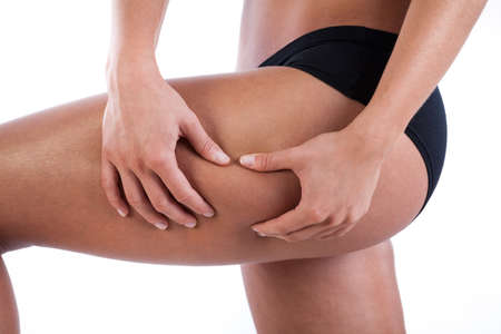 Woman watching her thigh to find cellulite photo