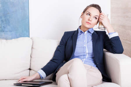 Young tired woman in smart clothes sitting on a sofa with coffee photo