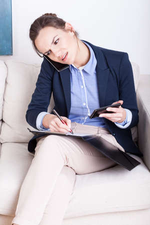 Woman sitting on sofa busy working holding two phones photo