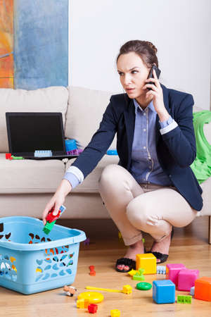 Young mother talking on phone and cleaning up toys Stock Photo