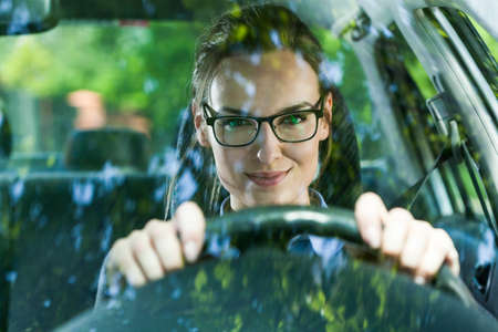 driving: Young attractive woman in glasses driving a car Stock Photo