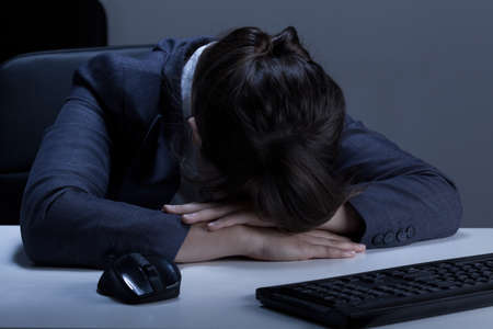 Woman sleeping in the office during overtime photo