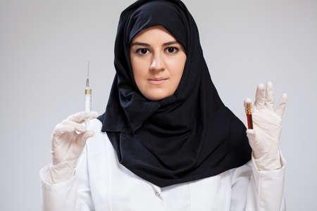 hijab: Muslim nurse holding in hands syringe and medicine