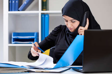 muslim woman: Muslim office worker looking for important document Stock Photo