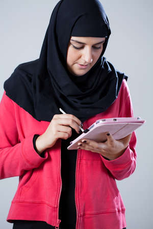 arab girl: Arab girl wearing head cover using tablet Stock Photo