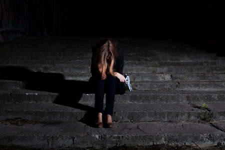 Woman with a gun in the darkness photo