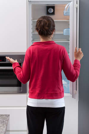 Girl in tracksuit opening the empty refrigerator photo