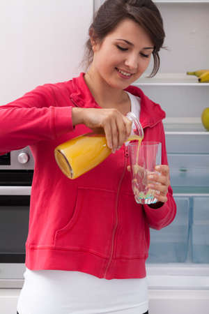 Young girl pouring orange juice to glass