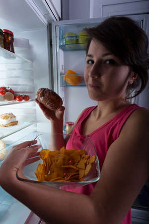 gula: La gula en la noche - mujer contra la nevera Foto de archivo