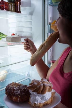 botanas: Muchacha que sufre de bulimia elegir los alimentos del refrigerador