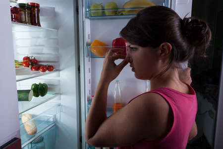 not open: Woman standing against the fridge holding nose Stock Photo
