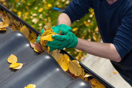 man cleaning: Cleaning the rain gutter during autumn, horizontal Stock Photo
