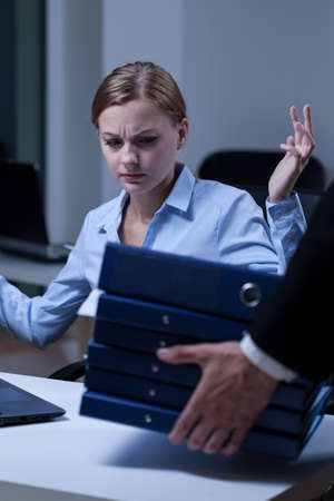 subservience: Young upset assitant and her work with documents Stock Photo