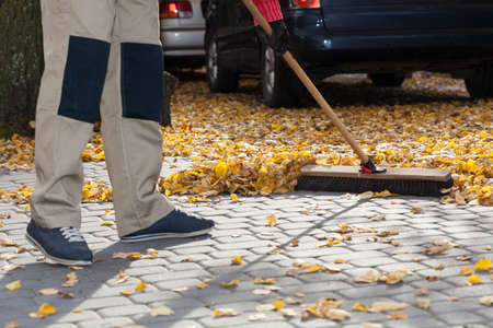 Horizontal view of brooming driveway from leaves Stock Photo - 32041465