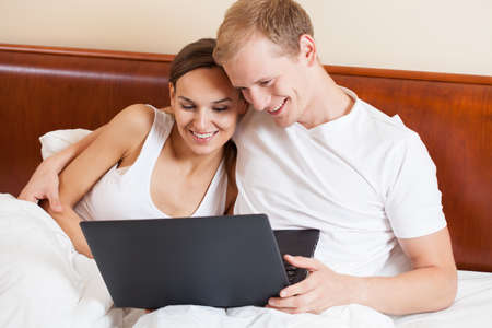 View of couple with laptop in bed photo