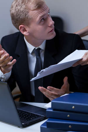 subservience: Young upset employee arguing with his boss at the office