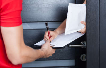 sign: Woman signing parcel shipment documents on clipboard Stock Photo