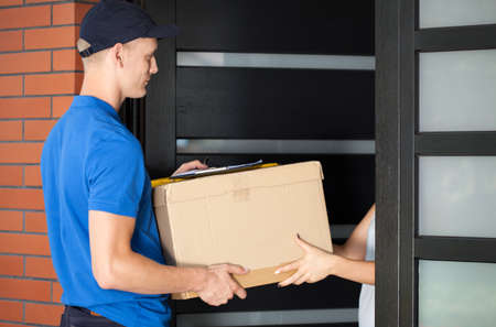 Woman receiving a parcel from a delivery huy