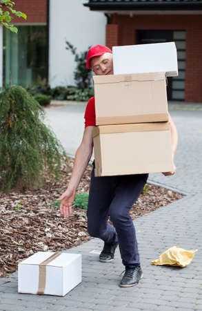 Delivery man picking up packages from the ground Reklamní fotografie