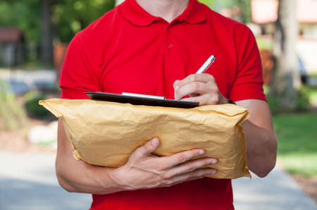 Delivery man filling in forms on parcel photo