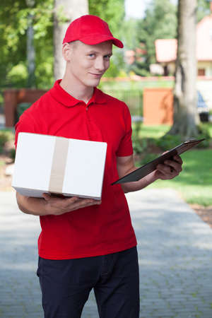 Delivery man holding a package and a clipboard  photo