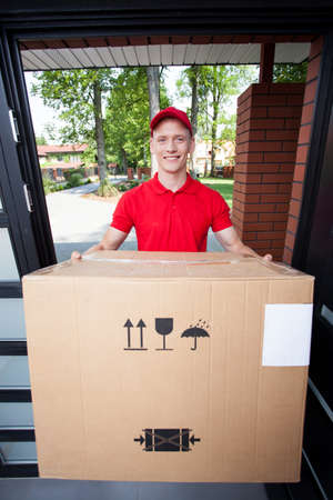 Delivery man handing in a large cardboard box photo