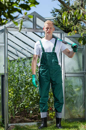 Young garden worker standing in front of glasshouse Stock Photo