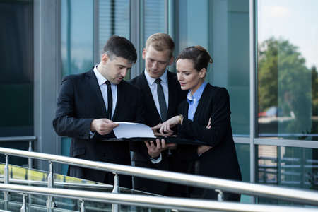 bank building: Group of businessman standing and reading papers Stock Photo