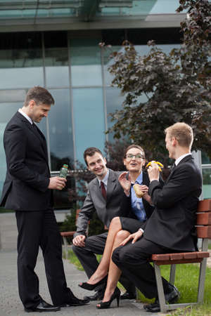 work break: Corporate coworkers sitting on a bench during break at work