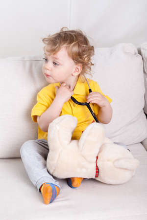 Child with stethoscope and teddy bear playing at doctor photo