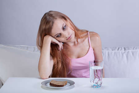 eating pastry: Portrait of young depressed girl with eating disorder