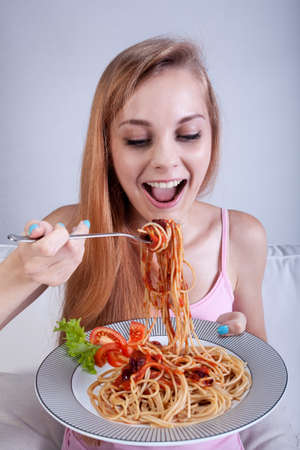 plateful: Young skinny girl eating a lot of spaghetti