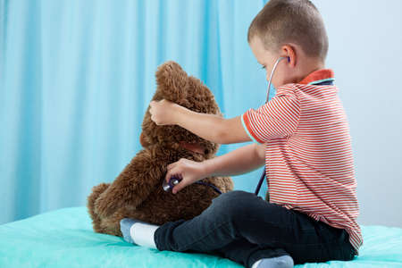 stethoscope boy: Child playing at doctor with his teddy bear