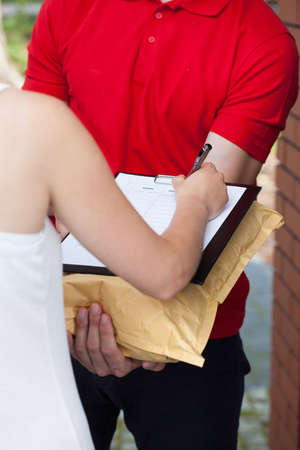 Delivery man with a package and woman signing documents photo