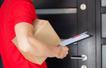 Delivery guy waiting at front door with a parcel Foto de archivo