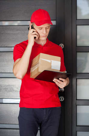 delivery man: Delivery guy with parcel calling a customer