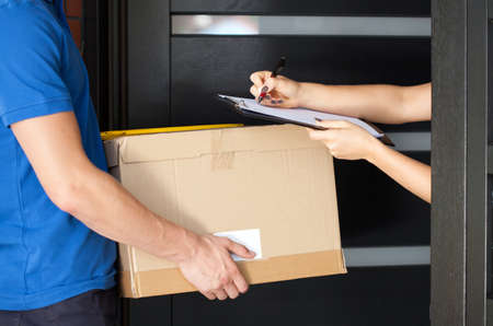 parcel service: Delivery guy holding package while woman is signing documents Stock Photo