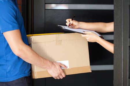 Lieferung Kerl hält Paket, während Frau Signieren von Dokumenten Standard-Bild