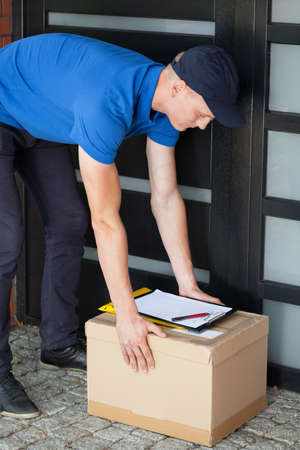Delivery guy leaving a parcel at the doorstep photo