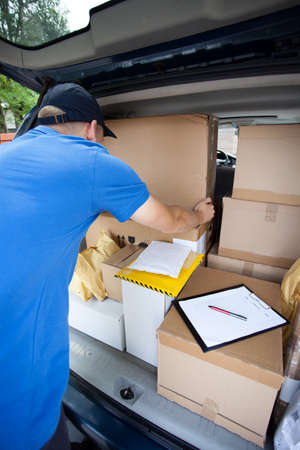 Delivery guy sorting through packages in his van photo