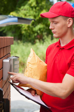 knock: Delivery man with parcel calling client on entryphone