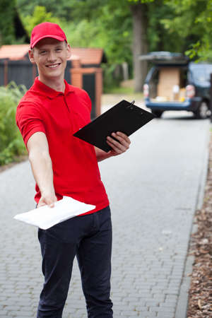 Delivery man giving a packet to his customer photo