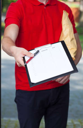 Delivery guy asking a client to sign a form photo